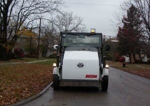 A street sweeper cleaning a residential street surrounded by fallen leaves
